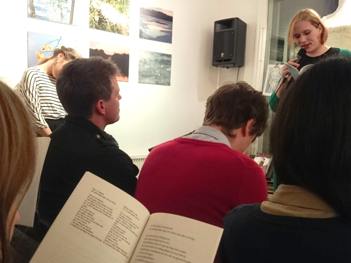 "Versopolis at Café Pilgatan: Katja Perat reading ""Engels"" while a member of the audience follows along with the translations."